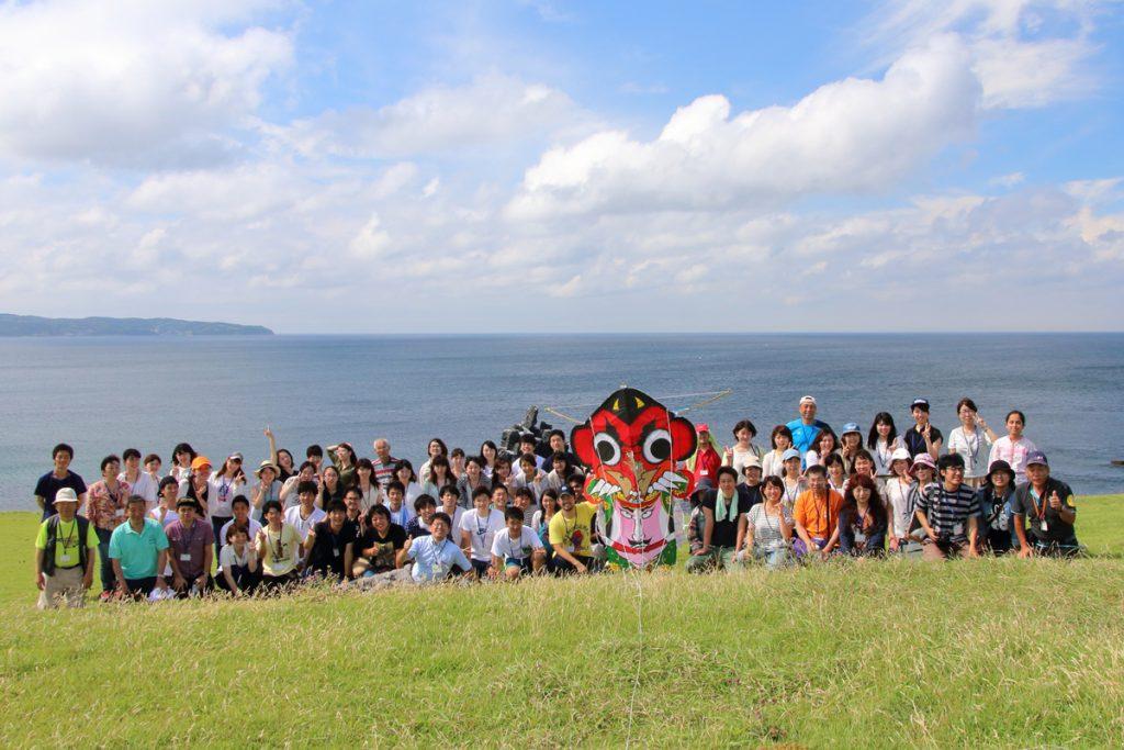 左京鼻をバックに壱岐の鬼凧(おんだこ)と参加者全員で記念写真